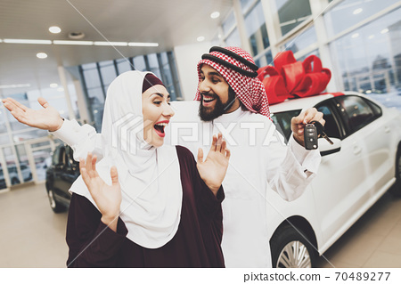 Couple at a car dealership standing and rejoicing. 70489277