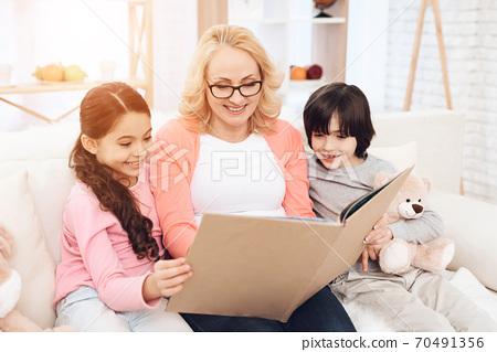 Grandmother with grandchildren reads a book. 70491356