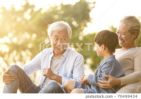 asian grandson, grandfather and grandmother sitting chatting on grass outdoors in park at dusk 70499434