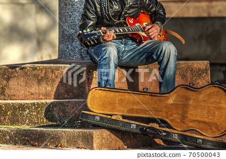 Guitar player playing on the street 70500043