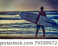 Surfer with surfboard by the shore 70500072