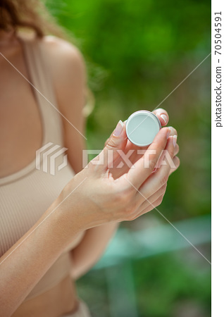 Close up of womns hands holding lip balm 70504591