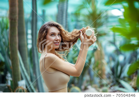 Long-haired pretty woman with a bar of soap in a greehouse 70504846