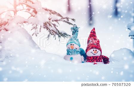 little snowmans on soft snow on blue background 70507320