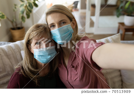 Senior woman and her daughter wearing face mask taking selfie at home 70513989