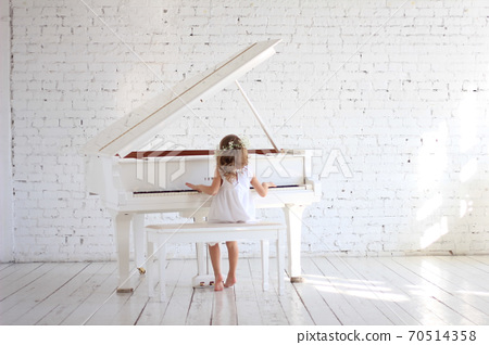 Girl in white dress playing piano in white hall with briks wall 70514358
