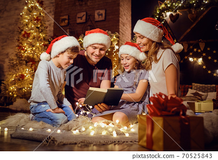 A family reads a book in a room in Christmas. 70525843