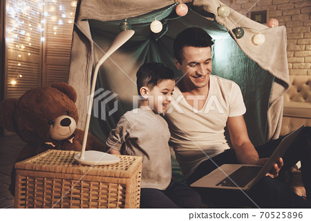 Dad and son at night looking at a laptop together. 70525896