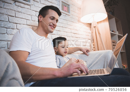 Dad sits with his son and works at a laptop. 70526856