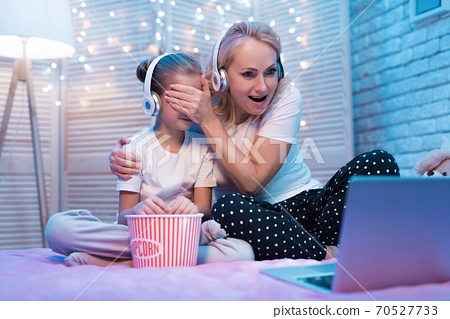 Grandmother and granddaughter are watching movie. 70527733