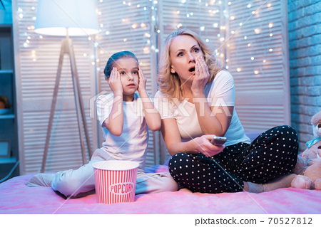 Grandmother and granddaughter are watching movie. 70527812