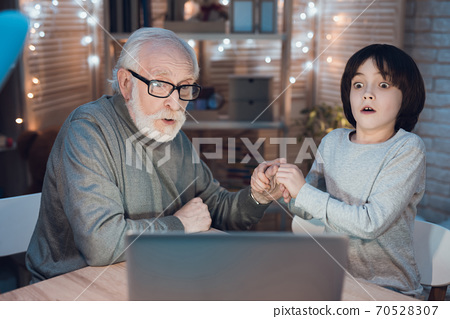 Grandfather and grandson holding hands.  70528307