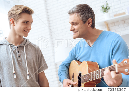 Father is playing on guitar and son is listening. 70528367