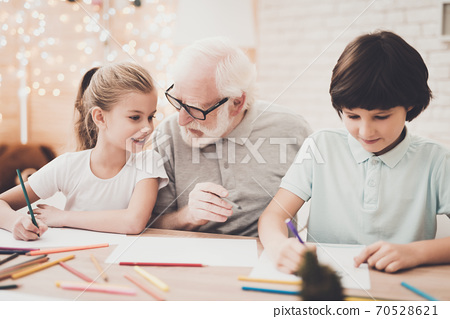 Grandfather, grandson and granddaughter at home.  70528621