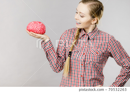 Woman thinking and holding fake brain 70532263