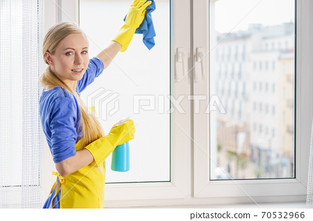 Woman cleaning window at home 70532966