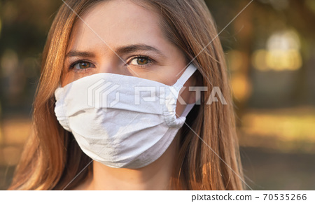 Young woman wearing white cotton virus mouth nose mask, nice bokeh in background, closeup face portrait 70535266