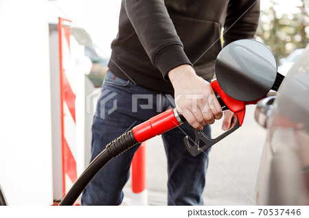 transportation and ownership concept - man pumping gasoline fuel in car at gas station 70537446