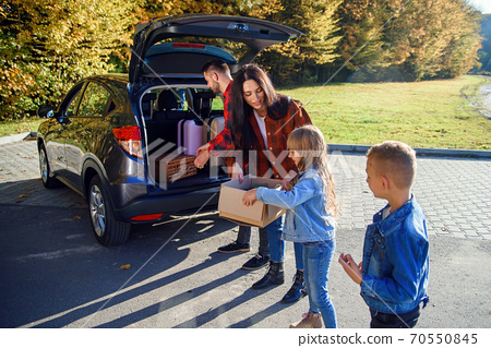 High-spirited likable parents unloading the auto's trunk with their cute 10-12s kids during moving into new apartment. 70550845
