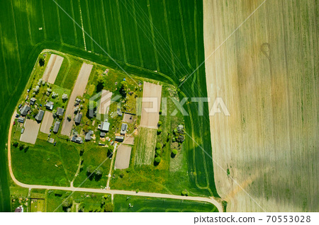 top view of a sown green field and a small village in Belarus. Agricultural fields in the village.Spring sowing in a small village 70553028