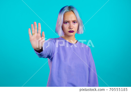 Pretty woman with violet hair disapproving with NO hand sign gesture. Denying, rejecting, disagree 70555185