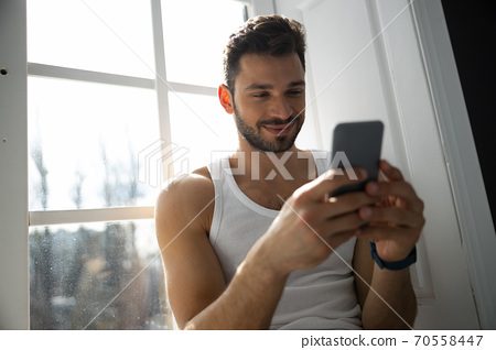 Cropped shot of man sitting on windowsill with mobile phone 70558447