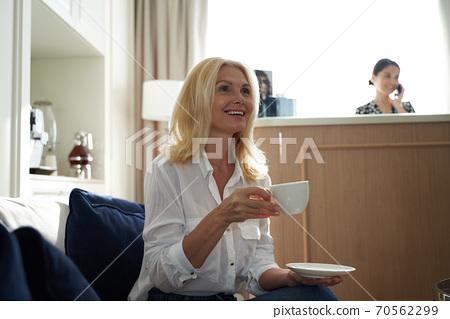 Beautiful adult woman enjoying hot drink in spa salon 70562299
