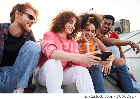 Cheerful friends using smartphone on urban roof 70562817