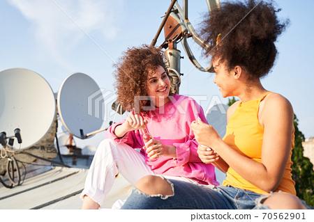 Two happy women drinking wine on roof 70562901