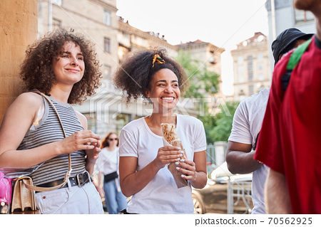 Cheerful young people enjoying fast food outdoors 70562925