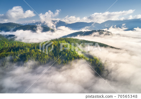 Mountains in clouds at sunrise in summer. Aerial view 70565348