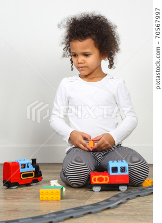 little girl playing with children's railway 70567997