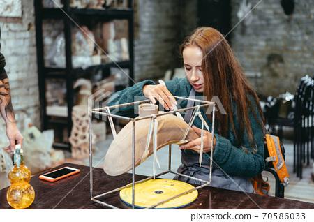 Portrait of young woman enjoying favorite job in workshop. 70586033