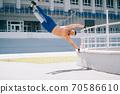 Young athletic man performs gymnastic elements - human flag. 70586610