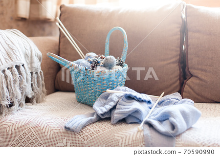 Knitting in cozy home interior. Knitted clothes, blue wicker basket with yarn, woolen balls, needles on sofa in warm 70590990