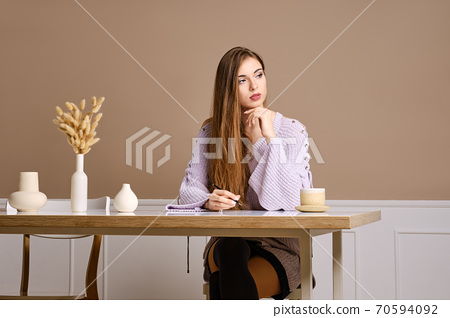 Young woman sits behind the table and thinking about what to write in postcard 70594092