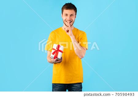 Happy man holding gift box at studio, portrait 70598493