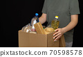 Volunteer putting food in a donation box 70598578