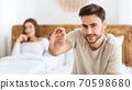 Focus on blue pill in hands of happy young man, and smiling wife sits in bed in modern interior of bedroom 70598680