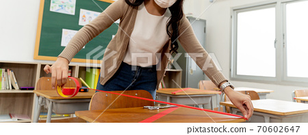 Female teacher using a red tape on the desks in classroom in primary school to keep social distancing measure policy in education building for Covid19 new normal concept 70602647