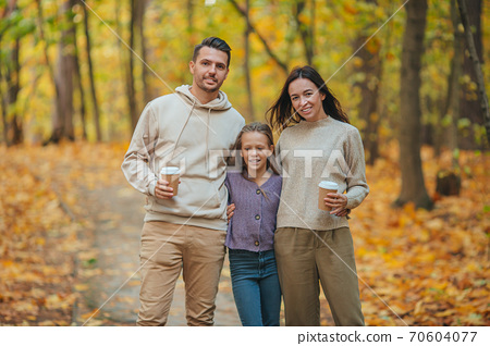 Portrait of happy family of three in autumn day 70604077