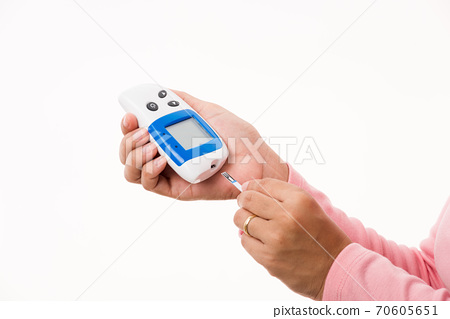 woman measuring glucose test level checking on finger by glucometer 70605651