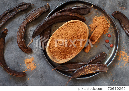 Dry carob pods and powder top view 70610262
