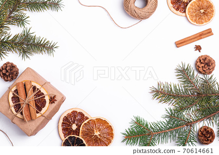 Christmas composition with handmade kraft paper gift box, dried citrus slices, cinnamon, anise, pine cones and fir tree branches, top view copy space 70614661