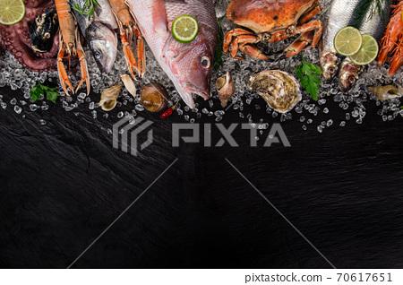 Fresh tasty seafood served on black stone table. 70617651