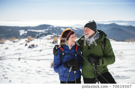 Senior couple hikers with nordic walking poles in snow-covered winter nature. 70619307