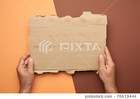 two male hands hold a blank torn piece of brown paper 70619444