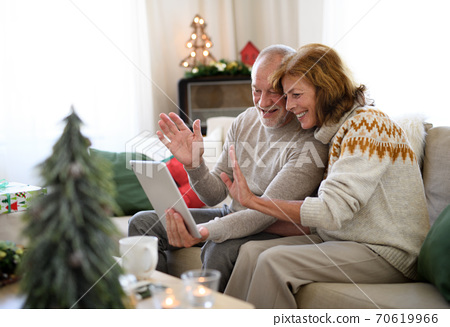 Side view of senior couple indoors at home at Christmas, having video call with family. 70619966