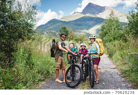 Family with small children cycling outdoors in summer nature. 70620238