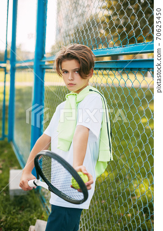 Portrait of a beautiful teenage boy standing with a tennis racket and a ball in his hands. Tennis player resting after training. Sport, sportsman, lifestyle, leisure 70625450